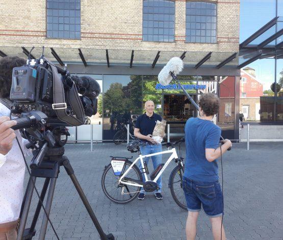 Jürgen Möller (Vorstandsvorsitzender) im Interview mit dem NDR-Fernsehteam vor einer der teilnehmenden Flensburger Bäcker-Filialen.