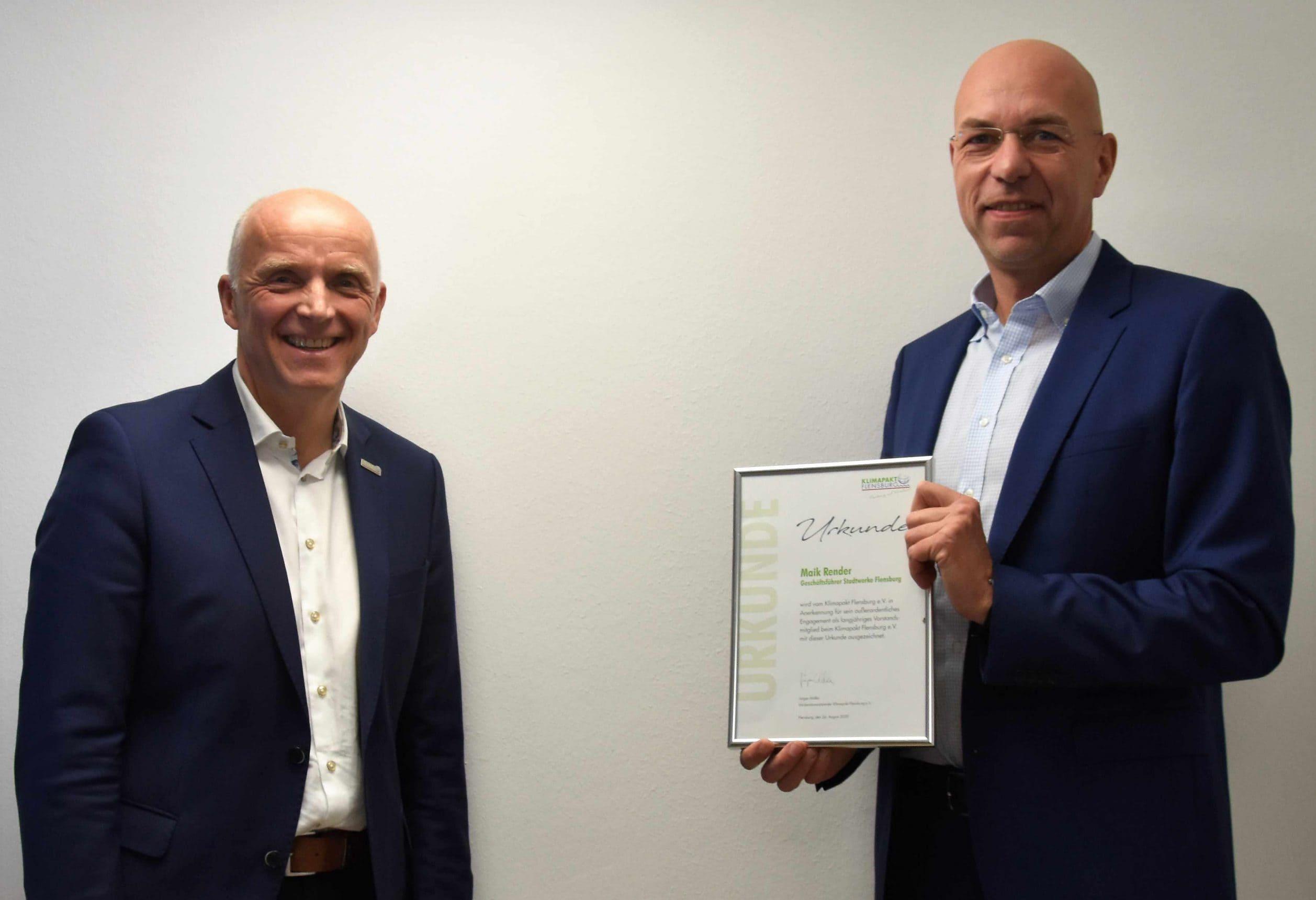 Jürgen Möller (Klimapakt-Vorsitzender, links) überreichte Maik Render (Geschäftsführer Stadtwerke Flensburg) eine Urkunde als Dank für die gute langjährige Vorstandsarbeit im Klimapakt Flensburg e.V.