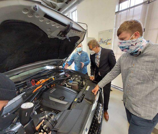 Sie sind Mangelware: Die beiden Studierenden im Masterstudiengang in der beruflichen Fachrichtung Fahrzeugtechnik Nicolay Tank (vorne rechts) und Tim Tilger (hinten links). Wirtschaftsminister Dr. Bernd Buchholz lässt sich von ihnen das Innere eines Hybrid-Fahrzeugs erklären.