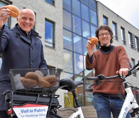 """Sie freuen sich über die kostenlosen """"Danke-schön-Brötchen"""": Jürgen Möller (Klimapakt-Vorsitzender, links) und Till Fuder (Klimaschutzmanager)."""